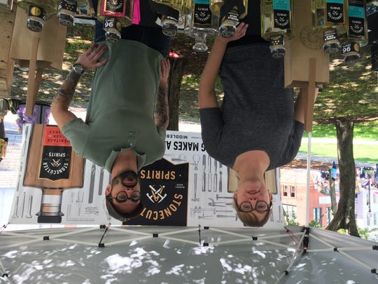 Stonecutter Spirits co-founder Sas Stewart mans the booth at the Burlington Farmers' Market with sales rep Jeff Lemieux on Saturday, June 24, 2017.
