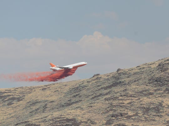 A firefighting aircraft drops flame retardant onto the Earthstone Fire on Monday afternoon.