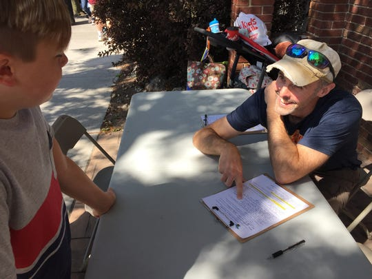 Mike Salowitz, right, interviews Jensen Stiers of Fenton as part of a guitar and ukulele giveaway at Thumbfest  in 2017.