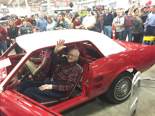 Harry Donovan of Indianapolis waves to well wishers after the new paint job on his 1967 Mustang was unveiled at the World of Wheels  car show in February.  The car is being restored for the WW II veteran at no cost after Donovan was ripped off by another man he paid to do the work.