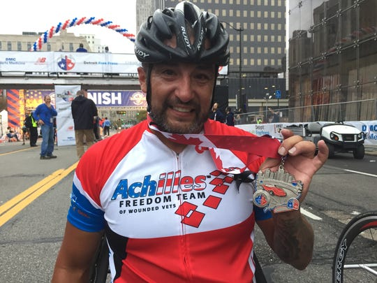 """Omar Duran, 38, of Clearwater, Fla., shows off his medal after coming in first among the hand cycle marathoners in today's Detroit Free Press/Chemical Bank Marathon -- with a time of about 1 hour, 22 minutes -- despite having the left handle of his hand crank come off in the last mile. """"I just held onto what was left and kept going,"""" he said."""