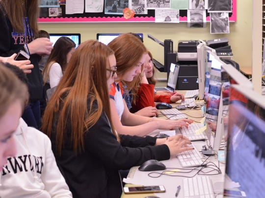 Staff of the Reno High School yearbook club work at a bank of computers.
