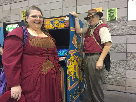 Melinda and Matt Bethke of Mesa pose for a photo with the Ms. Pac Man arcade game they were playing at Phoenix Comic Fest in Phoenix on Friday, May 25, 2018.