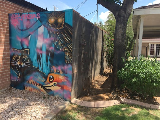 A spray-painted mural of desert animals sits tucked