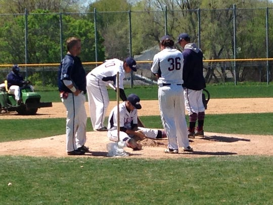 Members of the AIB baseball team prep the pitcher's