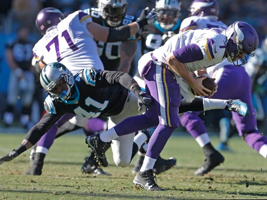 Minnesota Vikings' Case Keenum (7) escapes the tackle of Carolina Panthers' Captain Munnerlyn (41) during the first half of an NFL football game in Charlotte, N.C., Sunday, Dec. 10, 2017. (AP Photo/Bob Leverone)