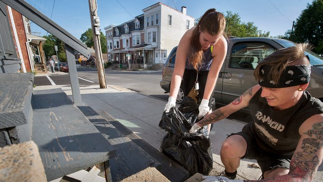 Catie Myers and Steve Klinedinst clean trash out between two steps during a Punks for Positivity clean up Sunday May 24, 2015 in the area of South Belvidere and West Princess Street in York.