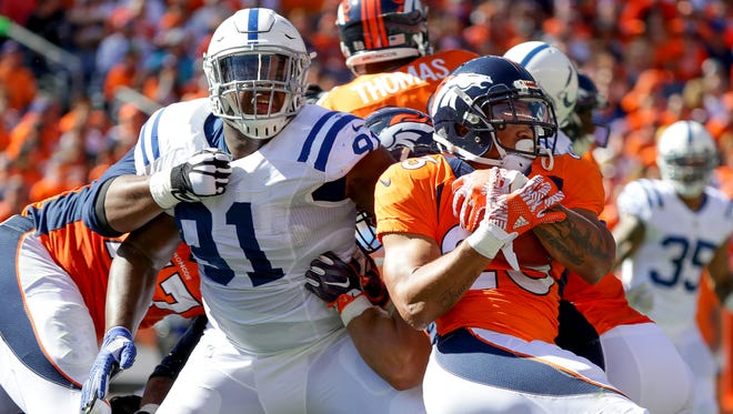 Denver Broncos running back Devontae Booker (23) breaks a tackle by Indianapolis Colts defensive tackle Hassan Ridgeway (91) during the second quarter at Sports Authority Field at Mile High in Denver on Sunday, September 18, 2016.