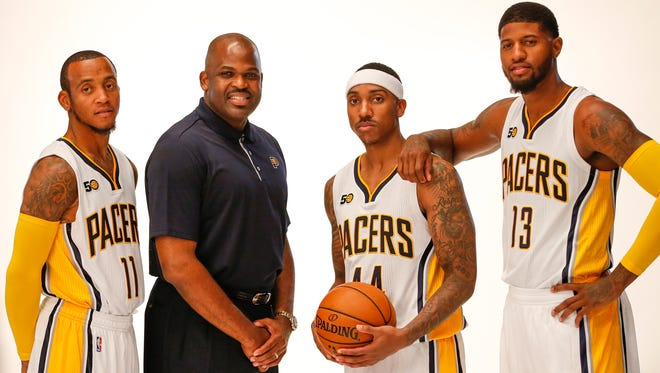 Indiana Pacers guard Monta Ellis (11), head coach Nate McMillan, guard Jeff Teague (44) and forward Paul George (13) smile for a portrait during media day at Bankers Life Fieldhouse on Sept. 25, 2016.