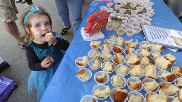 Rosmary Acker, 2, tastes Jewish foods at the Asheville