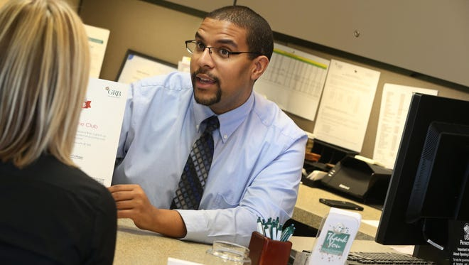 Senior personal banker Jamar Mattox works with a client at Genesee Regional Bank's Pittsford office.