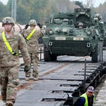 Members of the US Army 1st Brigade, 1st Cavalry Division, unload Stryker armored vehicles at the railway station near the Rukla military base in Lithuania.