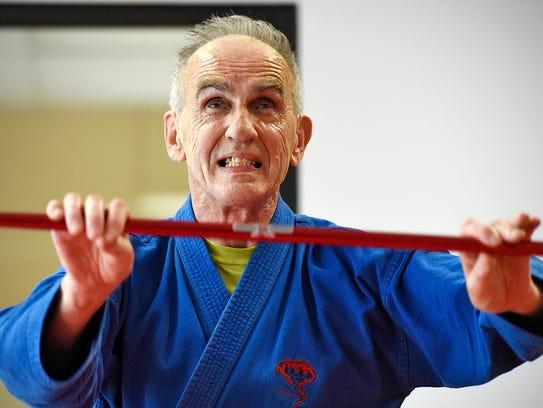 Black belt Ray Dinius works on a series of self-defense