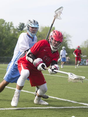 A CVU player and South Burlington player fight for possession during a high school boys lacrosse game Saturday morning. CVU won 10-6.