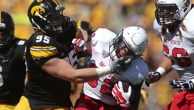 Iowa right end Drew Ott stops Ball State halfback Jahwan Edwards on Saturday, Sept. 6, 2014, at Kinnick Stadium in Iowa City, Iowa.
