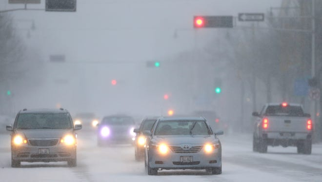 Traffic moves slowly along College Avenue in hazardous conditions Monday, December 28, 2015, in downtown Appleton, Wis. 