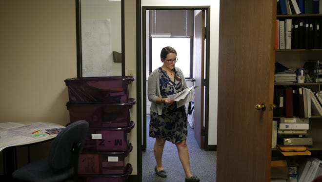 Stephanie Cheslock, 26, deputy clerk for Menasha, carries paperwork she is using in research for amending municipal code ordinance Friday, June 24, 2016 in Menasha, Wis. Danny Damiani/USA TODAY NETWORK-Wisconsin