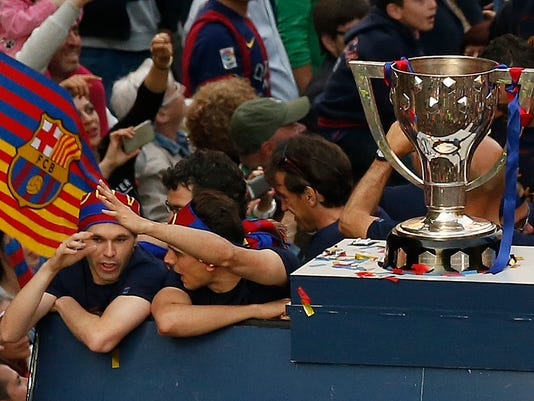 FC Barcelona's Andres Iniesta, left, rides on the top of a bus while celebrating with his team their victory in the Spanish league title in Barcelona, Spain, Sunday, May 15, 2016. (AP Photo/Manu Fernandez)