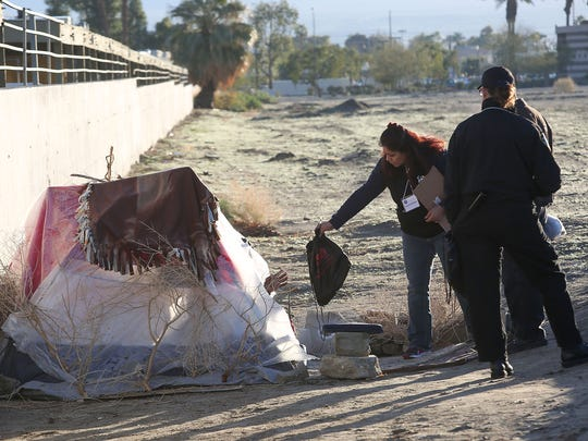 Rogelia Mejia hands a homeless man a bag of necessities in Indio while a group of volunteers was conducting a count of the valley's homeless, January 24, 2017.