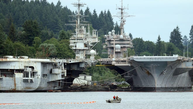 A Navy boat towing an orange boom is framed by the USS Independence and the USS Kitty Hawk while taking part in an oil spill drill in June 2015 in Sinclair Inlet.