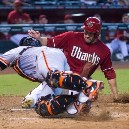 Arizona Diamondbacks' A.J. Pollock slides under Giants' catcher Andrew Susac to score in the fifth inning, as the D'Backs play the San Francisco Giants at Chase Field in Phoenix, on Wednesday, Sept. 17, 2014. The Giants defeated the D'Backs 4-2.