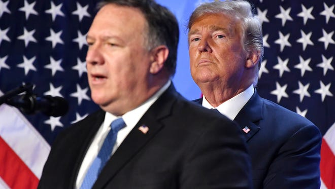 U.S. President Donald Trump, right, listens to U.S. Secretary of State Mike Pompeo during press conference after a summit of heads of state and government at NATO headquarters in Brussels, Belgium, Thursday, July 12, 2018. NATO leaders gather in Brussels for a two-day summit.
