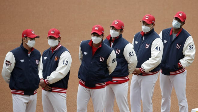 SK Wyverns players wearing face masks wait for the start of their regular season baseball game against Hanwha Eagles in Incheon, South Korea, Tuesday, May 5, 2020. Cheerleaders danced beneath rows of empty seats and umpires wore protective masks as a new baseball season began in South Korea. After a weeks-long delay because of the coronavirus pandemic, a hushed atmosphere allowed for sounds like the ball hitting the catcher's mitt and bats smacking the ball for a single or double to echo around the stadium.