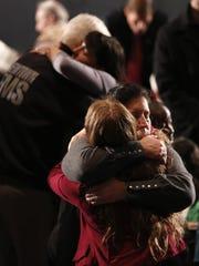Women embrace at a vigil held at Newtown High School