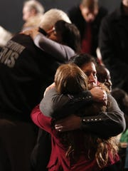 Women embrace at a vigil held at Newtown High School for families of the Sandy Hook Elementary School shooting victims in Newtown, Connecticut December 16, 2012. U.S. President Barack Obama is visiting Newtown High School to meet with the families of the victims and to thank first responders to the school shooting here, which was one of the deadliest such incidents in the nation's history.