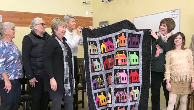 A quilt won last year by Pat and Dave Northington during the High Mountain Youth project's bed race comes home. The Northingtons were joined for the donation presentation by their granddaughter Kayleigh Rhodes. Accepting the gift were from left. volunteer Beth Rabourn, and board members Pam Tomlin, Laurie Benavides and Rita Combs.