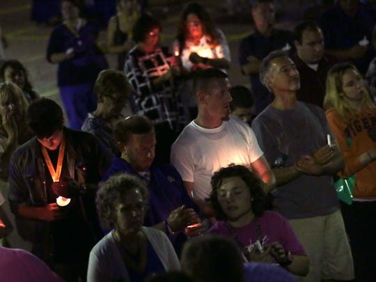 People pray during a candle lighting during the International Overdose Awareness Day in the Brickyard on Wednesday night.