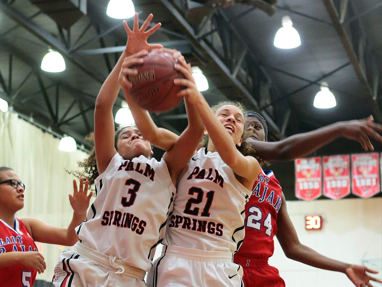 Palm Springs players Hannah Wright (3) and Joana Adams (21) both pull down a rebound against Indio during a Desert Valley League girls basketball game on Wednesday, January 14, 2015 in Palm Springs. Indio won, 57-44, and remain undefeated in league play.