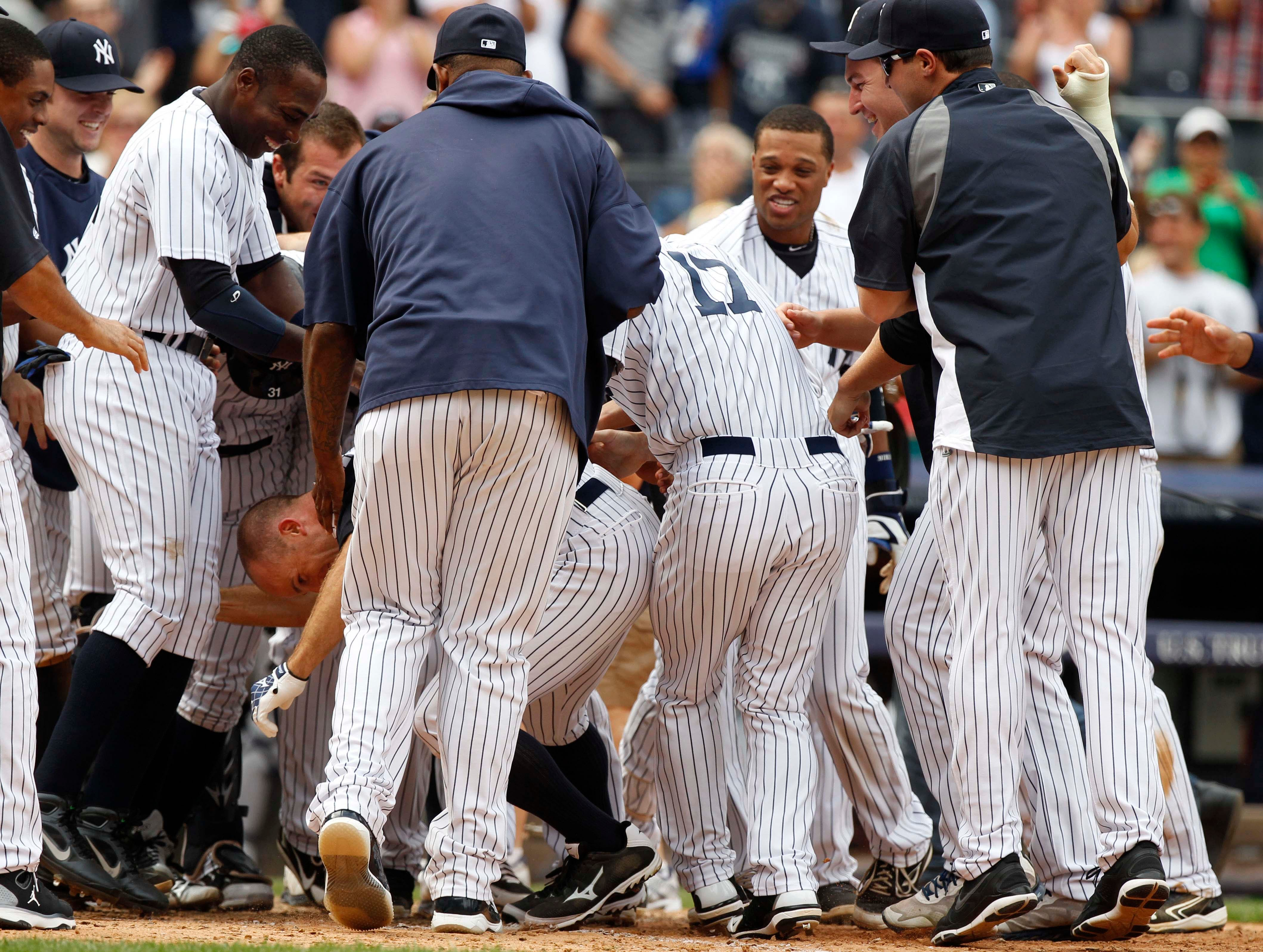 Aug. 11: Yankees center fielder Brett Gardner is mobbed at home plate by teammates after hitting a walk off home run against the Tigers at Yankee Stadium.