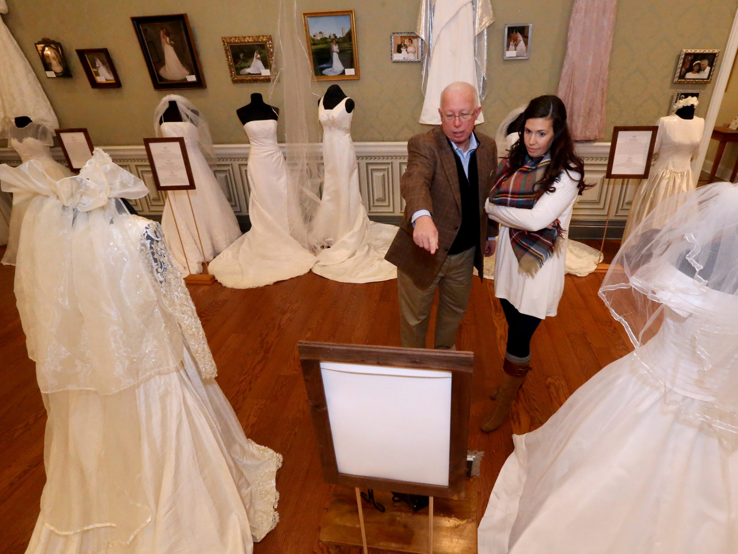 Mark Crocker and his daughter, Brittany Crocker Jackson, read over one of the bios of an exhibitor at the 'Wedding Dresses Through the Decades' display, which goes up Jan. 10.