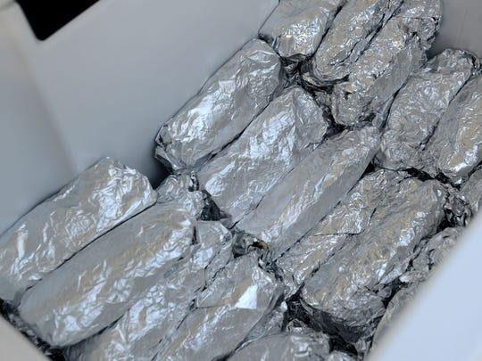 A cooler full of breakfast burritos.