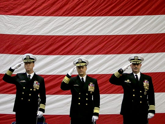 Saluting the flag are, from left, Capt. Kevin Lenox, Vice Admiral Mike Shoemaker and Capt. John Ring at the start of Thursday's change-of-command ceremony aboard the USS Nimitz at Naval Base Kitsap-Bremerton.