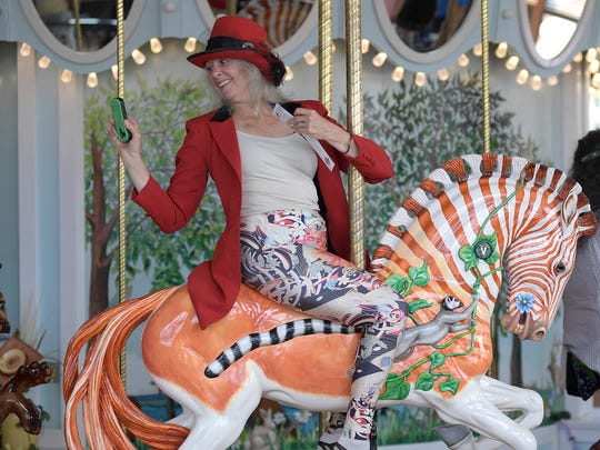 Nancy Hunter of Kings Valley, grabs a quick photo aboard Quigga a hand-carved Quagga while riding during the grand opening of Albany's Historic Carousel & Museum in Albany.