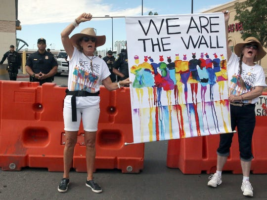 Demonstrators hold a banner in front of a barricade at the South-bound lanes to the Paso Del Norte International Port of Entry in downtown El Paso Saturday. The rally, which an organizer said drew and estimated 1,500 people closed traffic for about an hour. U.S. Customs and Border Protection officers watch in background.