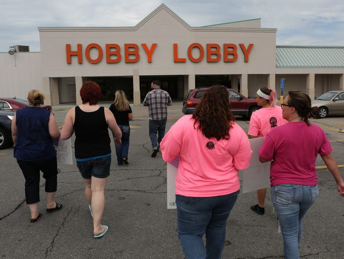 Protesters handed out flyers and condoms during a protest outside of the Hobby Lobby on Merle Hay Road in Des Moines on Saturday, July 12, 2014.