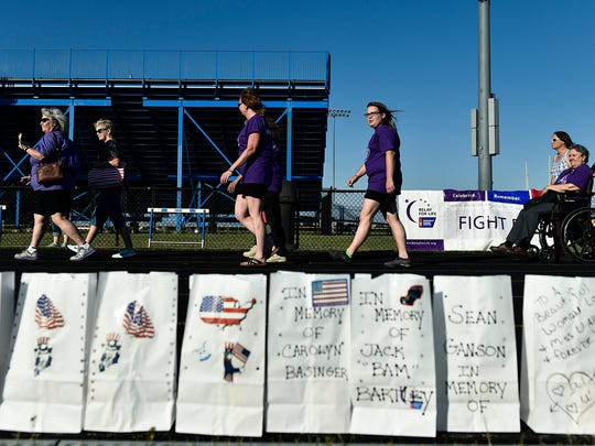 Survivors of cancer make their first lap around the track during the Relay For Life held at River Valley High School on Friday. The paper bags in the foreground are dedicated to those fighting cancer and to those who have died fighting cancer.