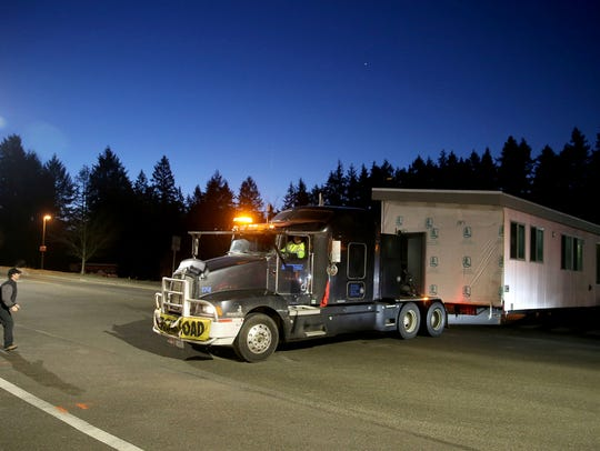 A modular home is backed into its temporary site off Highway 305 and High School Road on Bainbridge early Thursday morning. The two 70 foot by 30 foot boxes will be taken to a lot near Murden Cove and assembled into a home.