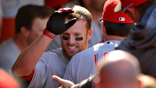 Cincinnati Reds' Zack Cozart celebrates with teammates in the dugout after hitting a two-run home run during the seventh inning.