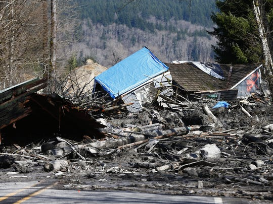 A house is seen destroyed in the mud on Highway 530 next to mile marker 37 on Sunday, March 23, 2014, the day after a giant landslide occurred near mile marker 37 near Oso, Wash.  At least six homes have been washed away, with three people reported dead so far and at least eighteen missing. The nearby Stillaguamish River has been dammed up by 15-20 feet of debris as a result, creating more flooding concerns, as reported by KING 5 via the state hydrologist.