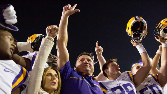LSU coach Ed Orgeron, center, celebrates with his team and his wife, Kelly, after an NCAA college football game against Mississippi in Baton Rouge, La., Saturday, Oct. 22, 2016. LSU won 38-21.