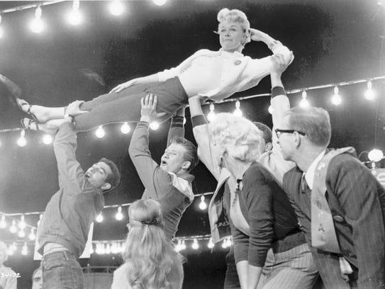 Cincinnati native Doris Day is hoisted aloft during