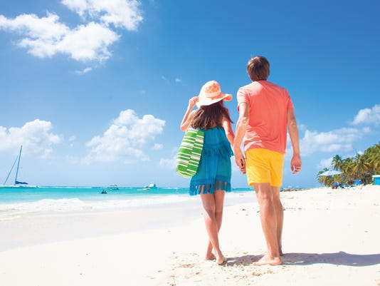 Couple wearing bright clothes at a tropical beach in Barbados