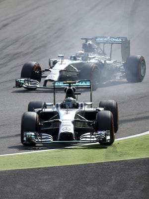 Nico Rosberg, foreground, drives off the track while his Mercedes teammate Lewis Hamilton overtakes him during Sunday's Italian Grand Prix.