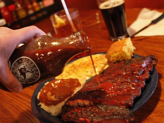 Some sauce is added to a half rack of ribs with sides of mac and cheese and mashed potatoes at Dinosaur Bar-B-Que in downtown Rochester.