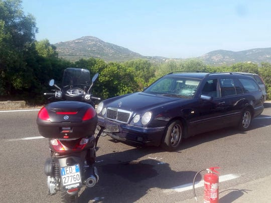 A scooter stands next to a car following an accident near Olbia, on the island of Sardinia, Italy, Tuesday, July 10, 2018. Actor George Clooney was taken to the hospital in Sardinia and released after being involved in an accident while riding his motorcycle, hospital officials said. The John Paul II hospital in Olbia said Clooney was released Tuesday. Local media that had gathered at the hospital said Clooney is believed to have left through a side exit. (Giovanna Sanna/La Nuova Sardegna via AP)