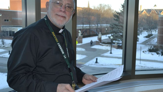 """The Rev. Andrew Ciferni sits in St. Norbert College's Center for Norbertine Studies, for which he is the director, overlooking the campus in the Mulva Library. Ciferni holds the song sheets for """"Sound the Bell of Holy Freedom,"""" which was selected to be the official hymn for the 2015 World Meeting of Families in Philadelphia. Ciferni wrote the hymn."""
